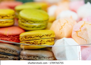 Multi-colored macaroons and meringues with cracks. Confectionery and sweets.