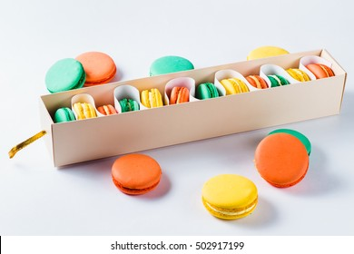Multicolored macaroons (orange, yellow and green) in a paper box.