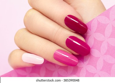 Multicolored manicure with different shades of pink nail Polish on women's hand.
