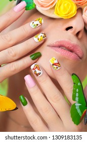 Multi-colored manicure on nails with a design of butterflies. Decorated glasses with flowers and butterflies on a girl with light lipstick. Nail art.
