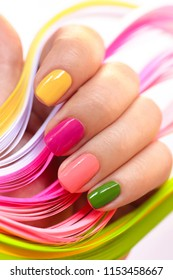 Multi-colored manicure with pink,green, yellow and peach nail Polish close-up.Summer bright manicure on short nails.