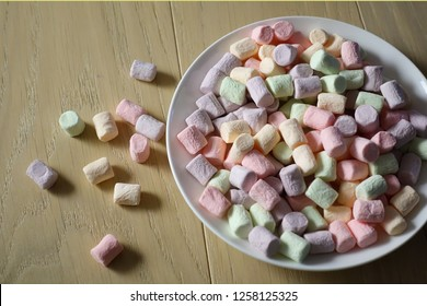Multicolored marshmallows on a white plate.