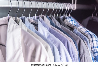 Multi-colored men's business shirts clothes on hangers in wardrobe, selective focus