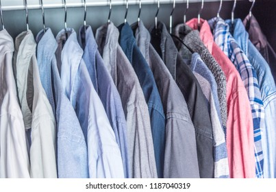 multi-colored men's business shirts clothes on hangers in wardrobe