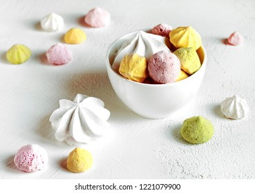 Multi-colored meringues in a white bowl on a white background