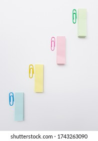 Multicolored metal paper clips on a white background.
