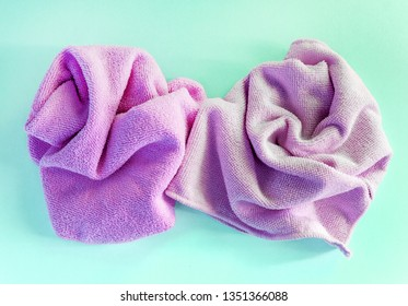 multicolored microfiber cloths are crumpled and lie on a turquoise background