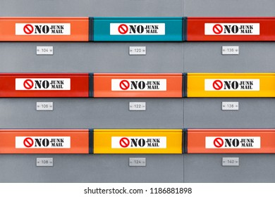 Multicolored modern mailboxes with no junk mail stickers on every box. Front view illustrative picture