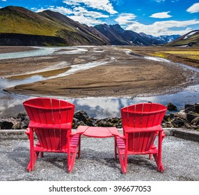 Multi-colored mountains from mineral rhyolite are lit with sun. Two red chaise lounges stand for tourists