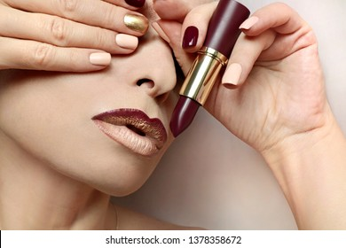 Multi-colored nail design.Trendy Burgundy nail Polish and lip makeup.Glamorous plum Burgundy lipstick.