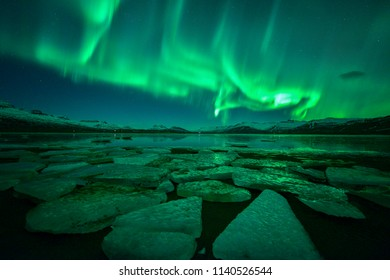 Multicolored northern lights over ice lagoon (Aurora borealis) ,A beautiful green aurora dancing with star at night, Iceland