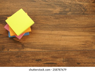 Multi-colored notepads laying on a wooden plank board surface with copy space
