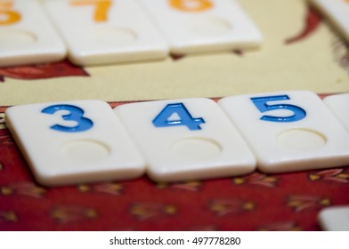 Multicolored numbered game tiles laying on a table cloth, in a mosaic style, focus centered on a set of three correlative tiles (3,4,5), with a shallow depth of field.
