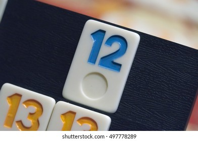 Multicolored numbered game tiles laying on a plastic rack simulating wood, in a mosaic style, focus centered on a number 12 tile, with a shallow depth of field.
