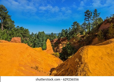 Multi-colored ocher outcrops - from yellow to orange-red. Roussillon, Provence Red Village. The picturesque canyon of ocher - natural dyes