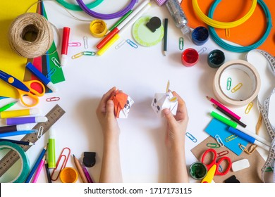 Multicolored office items on a white background and the origami