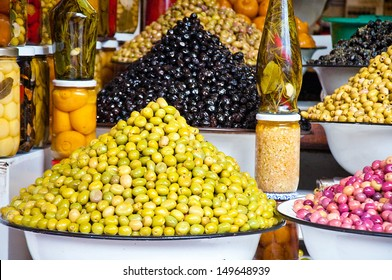 It is a lot of multi-colored olives and olive oil in the market