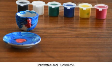 Multicolored paint tubs with painted miniature cup and saucer set on brown wooden background