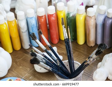 Multicolored paints and brushes on the table for creativity