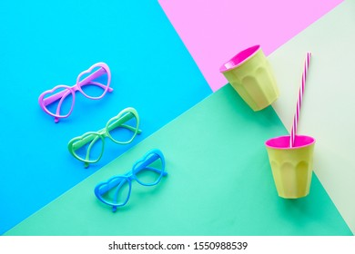 Multicolored paper background in pastel colors, flat lay, top view on three pairs of heart shaped glasses and plastic drinking glass with straw. Geometric diagonal creative flat layout.