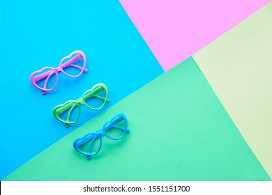 Multicolored paper background in pastel colors, flat lay, top view on three pairs of heart shaped glasses or sunglasses, geometric diagonal creative flat layout with copy-space.