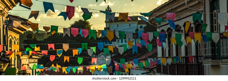 """Multicolored paper flags against sunset yellow sky during june party (""""festas juninas"""" in portuguese) in Brazil. In both sides and background, baroque colonial houses"""