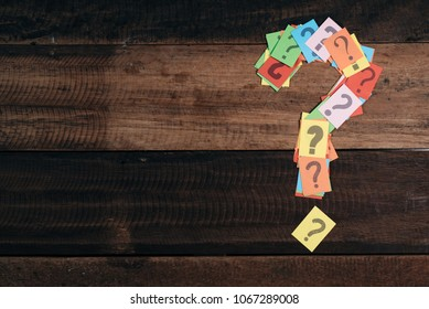 multicolored paper with QUESTION MARK on a wooden table background. questions,mystery and diversity concept. FAQ and Q&A background concept