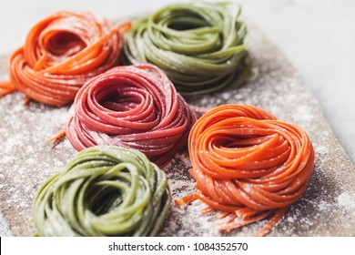 Multicolored pasta on a rustic cutting board over white table