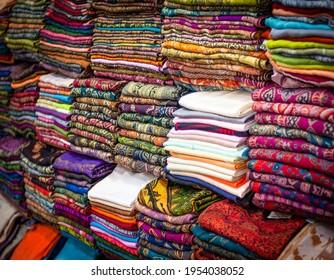Tissus à motifs multicolores sur un marché. Des piles de cadres complètes de tissus colorés.