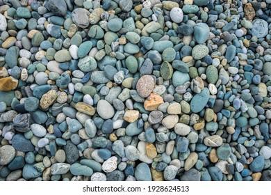 Multi-colored pebbles on the beach on the Black Sea. Pebble background. Coast. Pebble texture