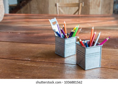 Multi-colored pencils and rulers in wooden pots on wooden boards.