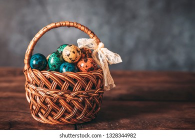 Multicolored perpelina eggs in an easter basket on a gray background.