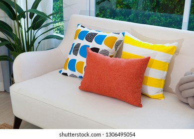 Multi-colored pillows on a beige fabric sofa in modern living room.
