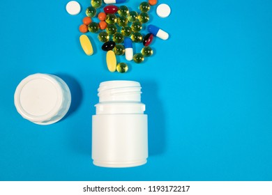 multi-colored pills and a bottle on a blue background