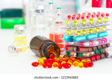 Multi-colored pills and capsules, medicine bottles, blood tubes.