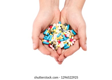 Multicolored pills in hands isolated on white background.