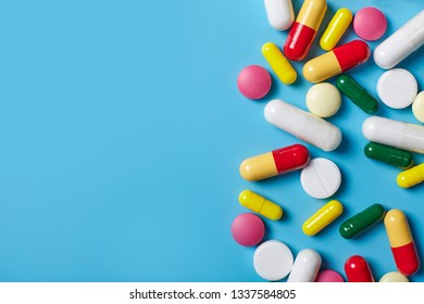 Multicolored pills on blue background with copy space. Medical concept. Texture.