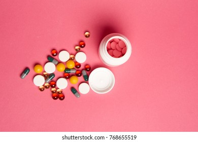 multicolored pills on a pink background