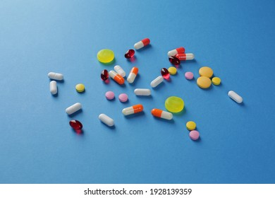 Multicolored pills of various shapes on a blue background. Close-up