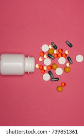 Multicolored pills, vitamins on a pink background