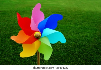 A multicolored pinwheel stands with a beautiful green grassy field