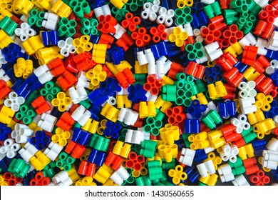 Multicolored plastic building blocks of the designer. Background of plastic colored details building blocks. Parts of bright small spare parts for toys. Top view.