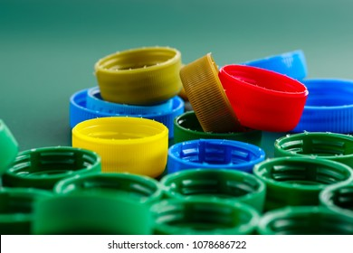 multi-colored plastic caps from bottles close-up on a green background