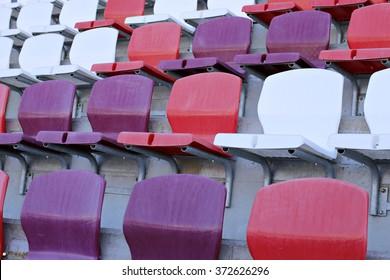 Multicolored plastic chairs on the stadium