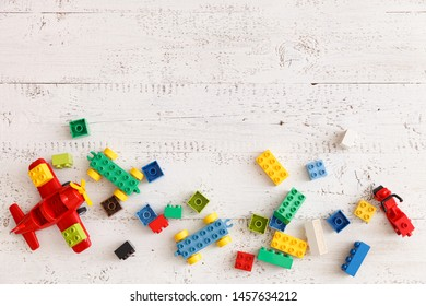 Multicolored plastic cubes scattered on a white wooden table. Top view of children's toys and other equipment. Educational games for children. Early development