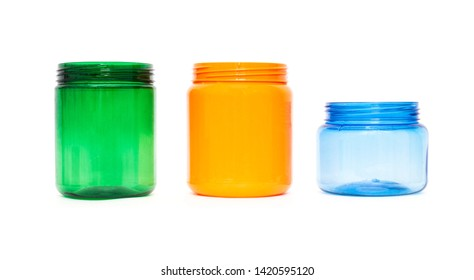 Multicolored plastic jars of orange, green and blue on a white background, high density polyethylene