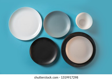 Multi-colored plates on a blue background, top view