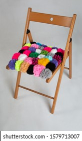 multicolored pompons on wooden chair on gray background