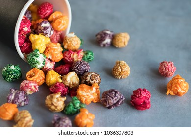 Multicolored popcorn and black paper cup on gray background. Soft focus.