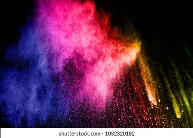 Multicolored powder explosion cloud isolated on black background. Freeze motion of color dust  particles splash.